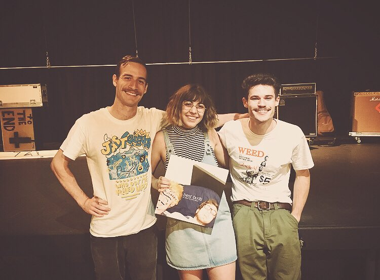 Amber Nicole holding the vinyl record for mom jeans' album best buds. She's smiling and standing between two members of the band with a mostly cleared off stage behind them.