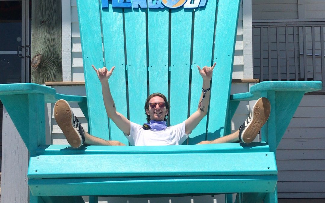 "Josh Rosenberg sits in a giant, blue adirondack chair with the word ""Hangout"" across the top and ""Gulf Shores, Alabama"" across the bottom."