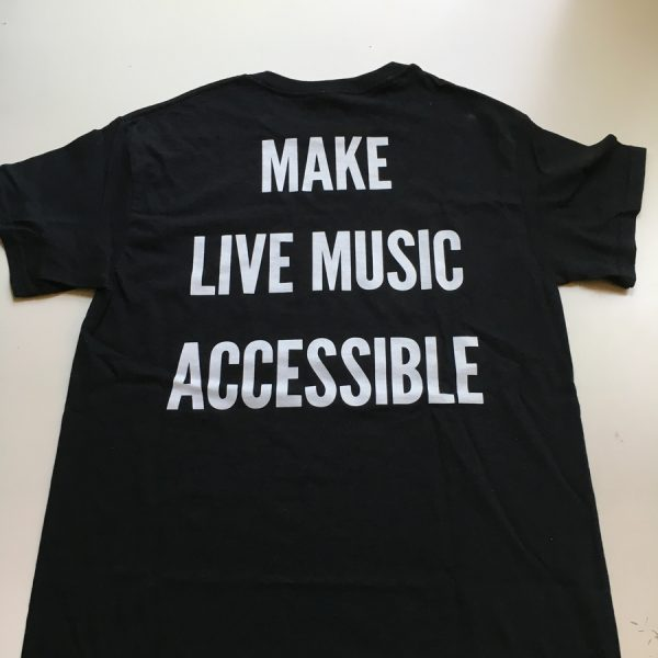 Make live music accessible in white text all caps down back of black t-shirt laying on table